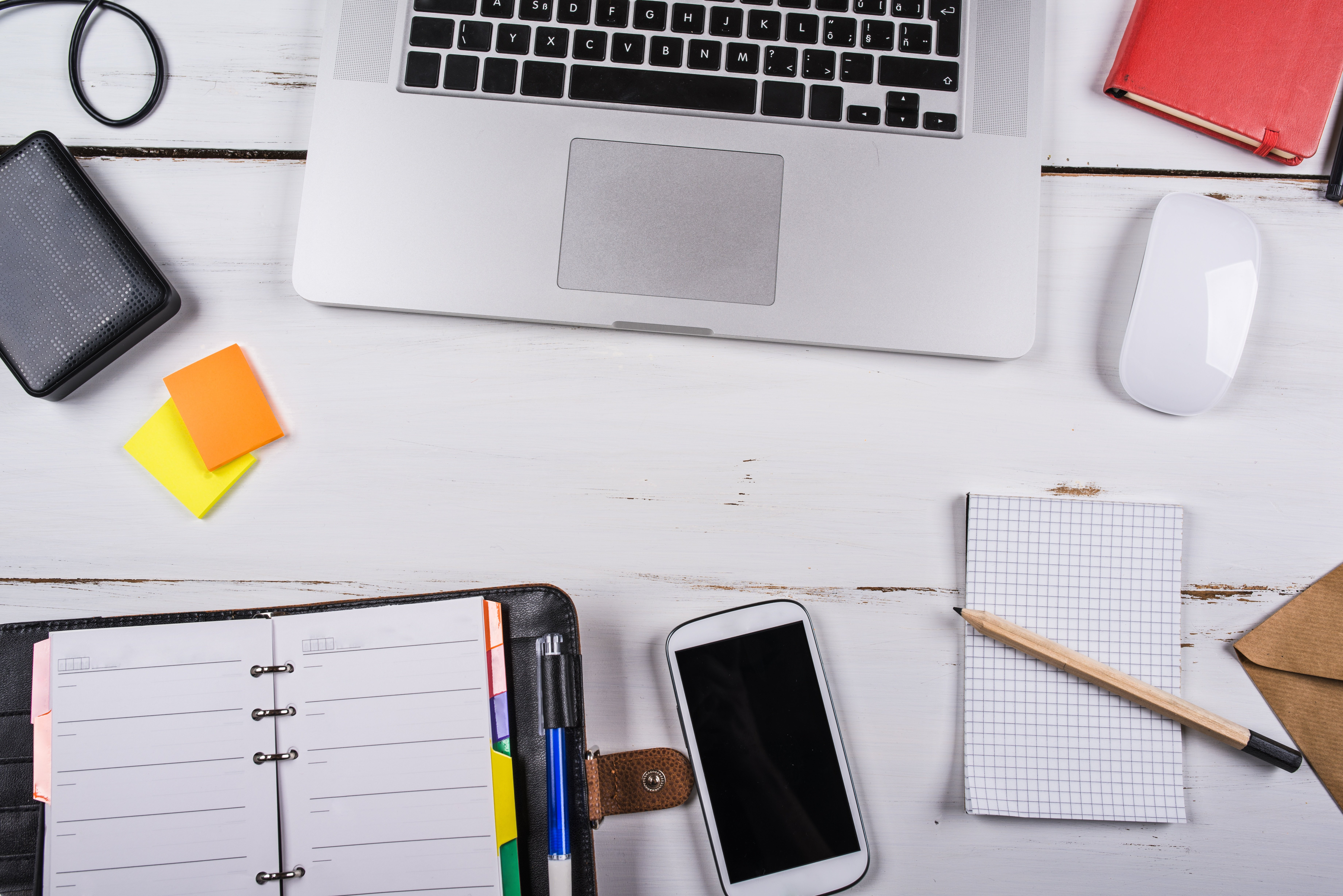 graphicstock-mix-of-office-supplies-and-gadgets-on-a-white-wooden-table-background-view-from-above_BCawXHTbb.jpg